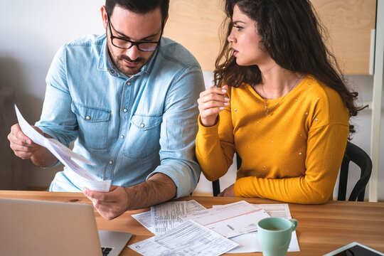 Worried husband and wife manage finances at home stock photo