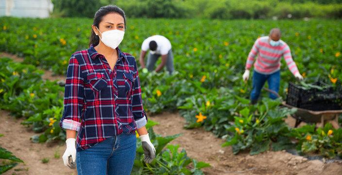 Portrait of latin american female farmer in protective mask on the farm field