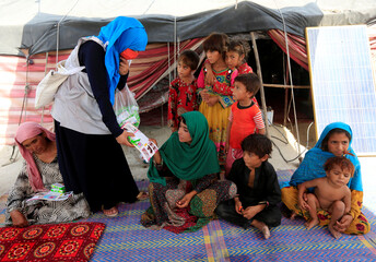 A UNICEF worker distributes brochures with medical tips to an internally displaced family at a makeshift camp, amid the coronavirus disease (COVID-19) outbreak, in Jalalabad