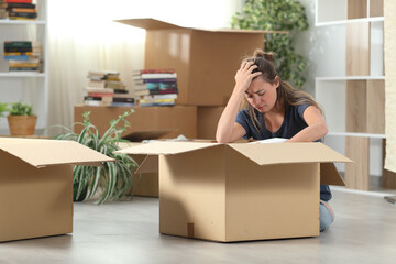 Sad evicted woman moving out packing boxes at home
