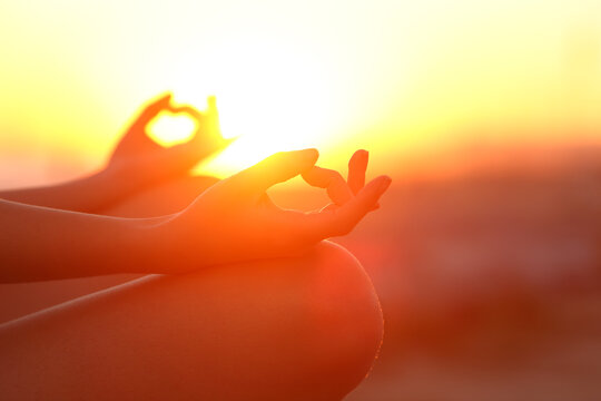 Woman hands doing yoga relaxing at sunset outdoor