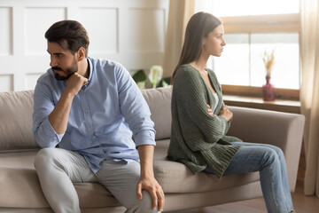 Unhappy angry stressed man and woman ignoring each other after quarrel, sitting on couch separately, sad upset girlfriend and boyfriend not talking, family crisis or relationship problems