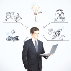 Businessman with laptop and drawing business idea sketch