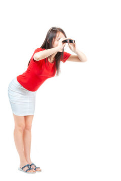 A young brautiful woman in a red blouse and white skirt, looking through binoculars, on a white background, isolated.