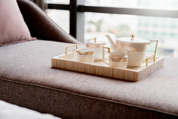 set of tea or coffee with small teapot on wooden trayon daybed sofa with room interior background ...