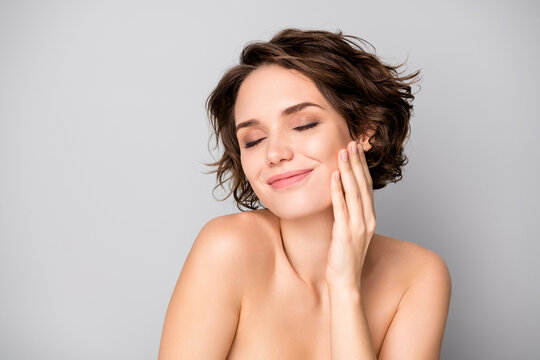 Portrait of positive lovely pretty girl touch hand face enjoy her soft pure perfect skin after bodycare plastic surgery treatment isolated over grey color background