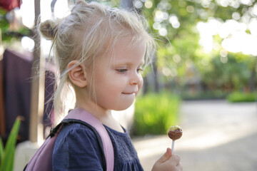 Outdoor portrait of adorable blonde toddler girl eating candy lollipop