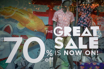 Sale sign in the window shop - seasonal shopping concept