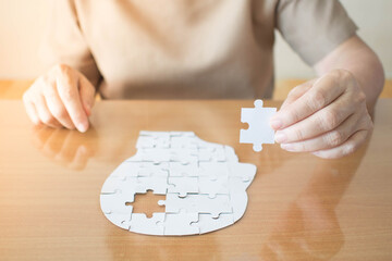 Wall Mural - Elderly woman hands holding missing white jigsaw puzzle piece down into the place as a human head brain shape. Creative idea for memory loss, dementia, Alzheimer's disease and mental health concept.
