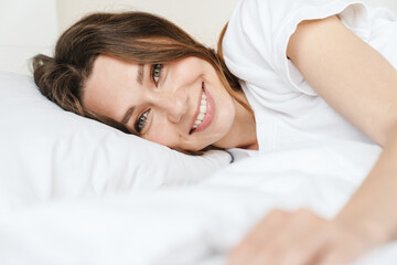 Image of beautiful caucasian woman smiling while lying in bed