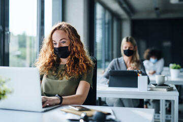 Deurstickers Wanddecoratie met eigen foto Young people with face masks back at work or school in office after lockdown.