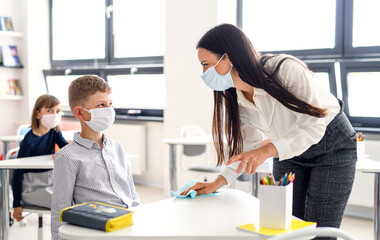 Teacher and children with face mask back at school, disinfecting desks.
