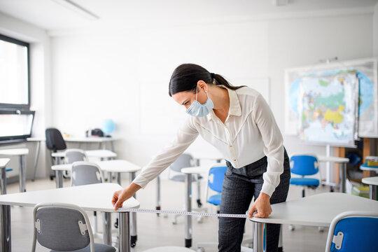 Teacher back at school after covid-19 quarantine and lockdown, measuring distance of desks.