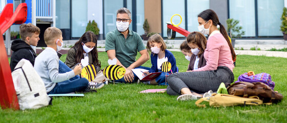 Group of cheerful children with face masks learning outdoors at school after lockdown.