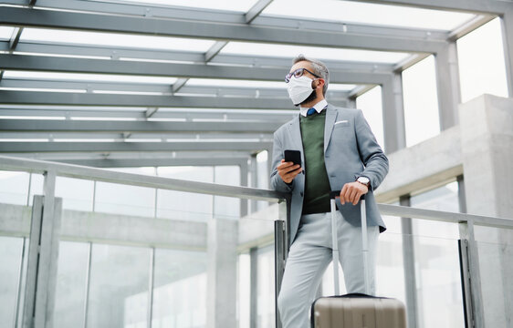 Businessman with luggage going on business trip, wearing face mask at the airport.