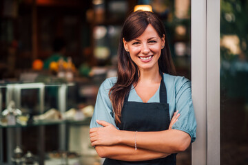 Portrait of a cheerful waitress standing in entrance of the shop.