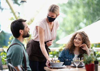 Waitress with face mask serving happy couple outdoors on terrace restaurant.