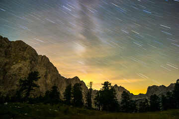 Wall Mural - Star trails night sky at twilight hour. Julian Alps, Triglav National Park, Slovenia, Mountain View from Mount Slemenova, Sleme to Mountain Jalovec.