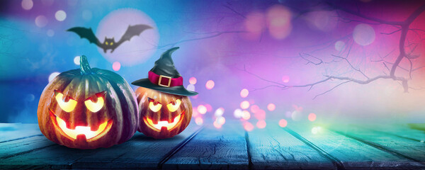Festive background decoration for Halloween in trendy blue purple tones. Two glowing pumpkins and bat on background of evening mystical forest, ultra wide format. Magical atmosphere with festive light Fototapete