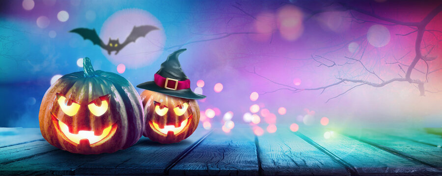 Festive background decoration for Halloween in trendy blue purple tones. Two glowing pumpkins and bat on background of evening mystical forest, ultra wide format. Magical atmosphere with festive light