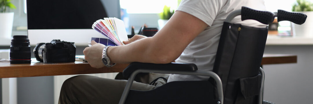 Close-up of professional designer working in office holding colourful palette. Male sitting in wheelchair. Photocamera and laptop on desktop. People with disability concept
