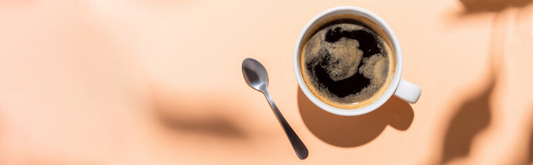 top view of coffee cup and teaspoon on beige with shadows, horizontal concept