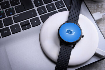 Smart watch on wireless charging with on-screen charging indicator. At the desktop, near at the laptop. Top view.