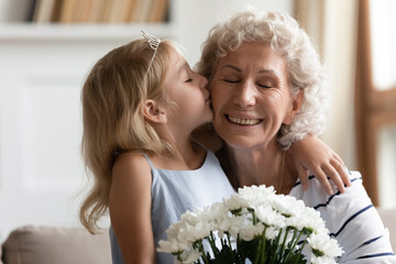 Close up image happy old grandmother closed eyes enjoy moment while her little granddaughter kisses on cheek and congratulates her with birthday presents flowers. Women 8-march Day, life event concept