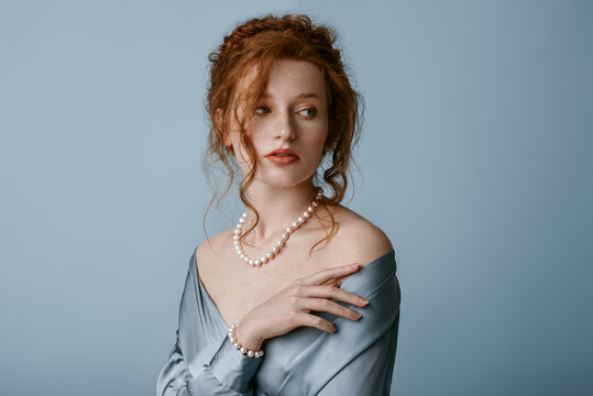 Beautiful elegant redhead freckled woman wearing luxury pearl jewelry set: necklace, bracelet, silk blouse, posing in studio, on blue background. Jewellery advertising conception. Copy, empty space