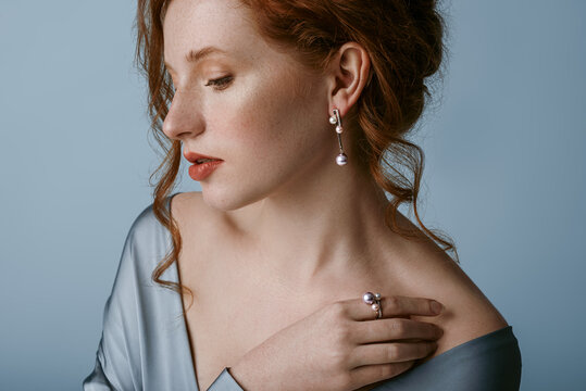 Beautiful elegant redhead freckled woman wearing luxury  pearl jewelry: earrings, ring, silk blouse, posing in studio, on blue background. Jewellery advertising conception. Close up profile portrait