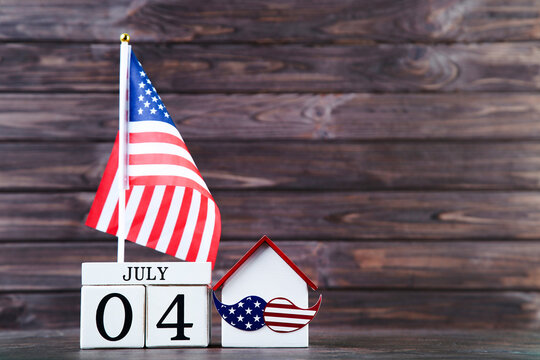 Independence Day concept. American flag with house model and cube calendar on wooden background