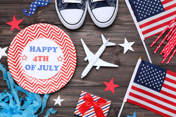 Text Happy 4th of July with flags, gift box, airplane model and paper stars on wooden table