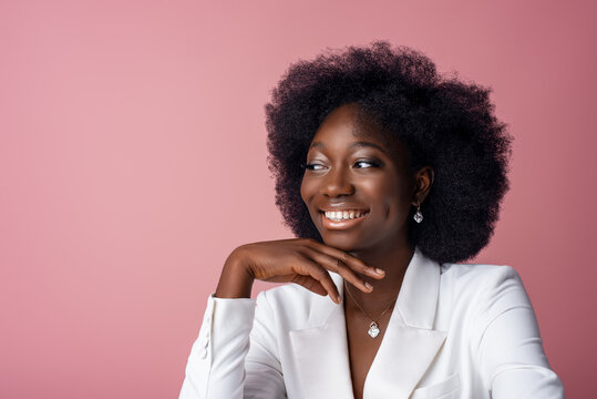 Yong beautiful happy smiling African American woman, model wearing elegant jewelry, white blazer, looking aside, posing in studio, on pink background. Close up portrait. Copy, empty space for text