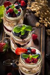 Tasty yoghurts with muesli, fresh berries and jam on wooden table. Healthy breakfast.