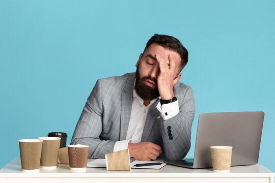 Working overtime. Exhausted businessman sitting at desk with laptop and empty coffee cups against blue background