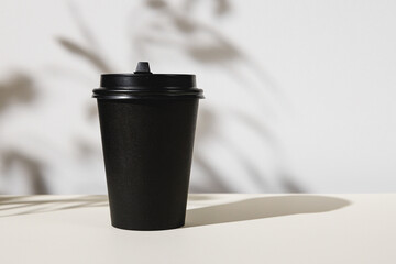 Takeout coffee cup with foliage shadows, copy space