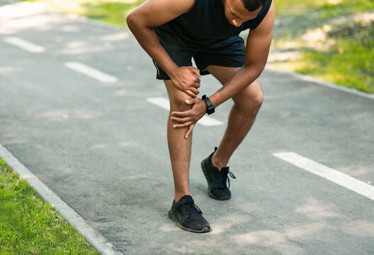 African American jogger suffering from pain in knee during his morning run at park