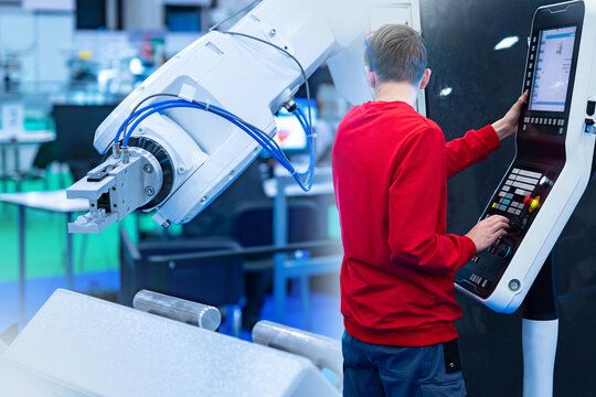 Robotics. A man in a red sweater sets up an industrial robot. The engineer at the control panel and the robot's white hand. Production automation. The task of the algorithms of actions for the machine