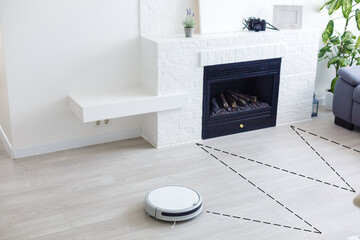 white robot vacuum cleaner cleans the floor from debris,home cleaning with an electric vacuum...