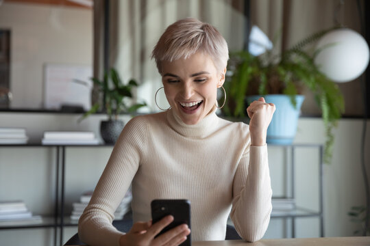Employee woman sit at desk holding smartphone use e-bank app check account balance feels happy. Salary day, online lottery user celebrating win, reward, great offer discount sales, e-commerce concept