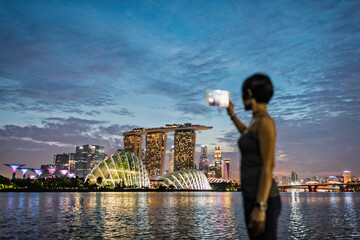 Asia, Singapore, young woman taking a photograph of the Singapore skyline, using a digital tablet, at dusk while on vacation