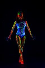 Female model with colorful ultraviolet body in dark