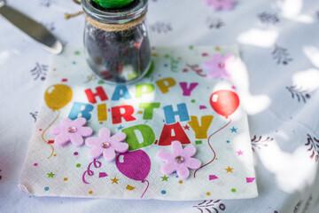 Papier Serviette auf einem Tisch mit den Worten – Happy Birthday – in englisch mit Tischdecke Besteck und Tischdekoration, Deutschland