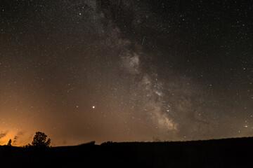 Sternenhimmel mit der Milchstraßen Galaxie im Sommer mit einem Baum vor einer beleuchteten Stadt,  Deutschland