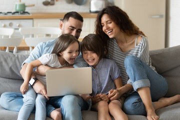 Canvas Prints Akt Close up happy parents with daughter and son using laptop sitting on couch at home. Smiling mother, father and cute children looking at laptop screen using video call. Family having fun with computer.