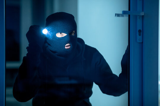 Intruder breaking in apartment or office using flash light