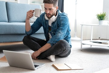 Handsome modern man designer working on laptop online, using internet at home