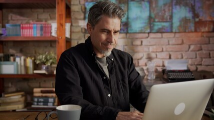 Portrait of happy mature man sitting at table using laptop at home working in home office.