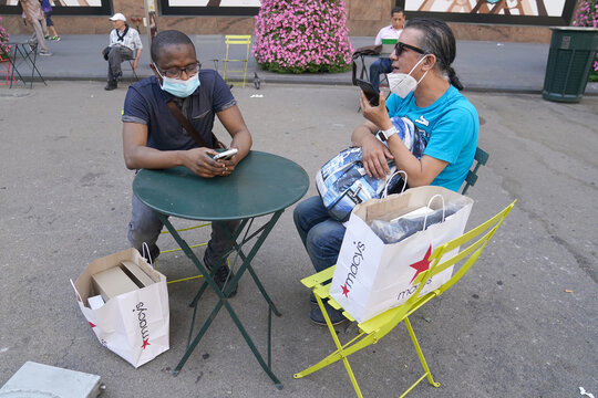 People sit with shopping bags outside of Macy's Herald Square store on the first day of the phase two re-opening of businesses following the outbreak of the coronavirus disease (COVID-19), in the Manhattan borough of New York City