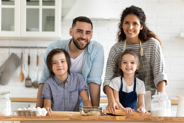 Close up headshot portrait picture of happy young couple with children cooking dinner looking at camera standing at table in kitchen. Smiling family using rolling pin for pastry on wooden board.
